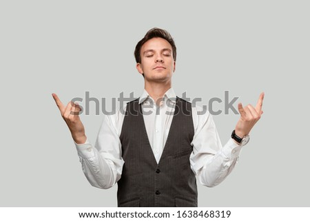 Confident businessman in a white shirt and grey vest holding hands in a gesture of rock music fan to express emotion of success. Concept of success #1638468319