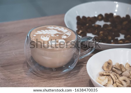 Coffee of cappuccino with FOX picture maked in latte art method in a glass vacuum cup on a wooden table top with bowls with dried fruits next to.