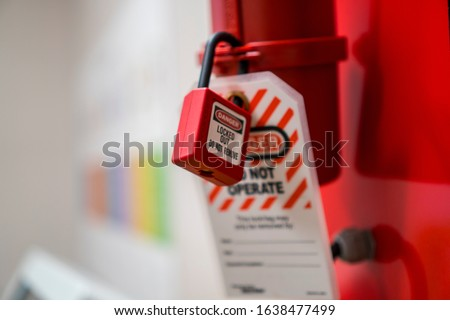 Lock Out, Tag Out with a danger tag. Electrical and machine system and safety equipment. There is a Danger and Do Not Remove warning. Plug Lock.