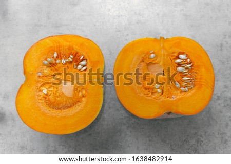 two halves of one pumpkin cut in half on a gray background, core, pulp and pumpkin seeds. #1638482914