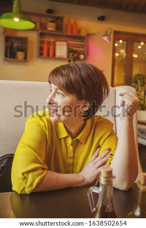 Beautiful mature woman in yellow shirt in cafe #1638502654