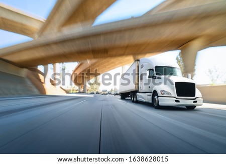 American style truck on freeway pulling load. Transportation theme. Road cars theme. Truckers heaven. Trailer passing the bridge #1638628015