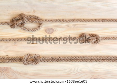 Marine knots used in yachting: figure eight knot, square knot, bowline knot. Nautical knots on wooden background. #1638661603