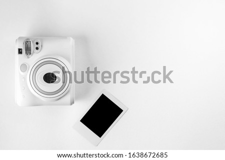 Modern instant camera, photo white wooden background. Top view, tender minimal flat lay style composition. fashion blogger, beauty technology. copy space