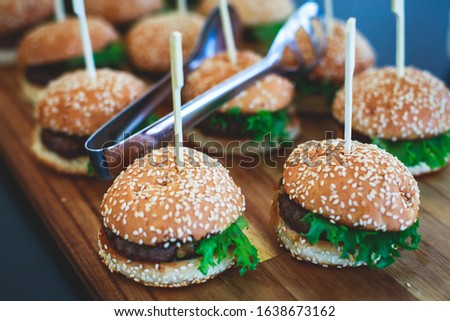 Beautifully decorated catering banquet table with variety of vegetables and different burger burgers snacks on corporate christmas birthday party event or wedding celebration  #1638673162