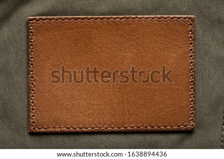 Blank brown leather label, macro close up. Leather patch with stitching #1638894436