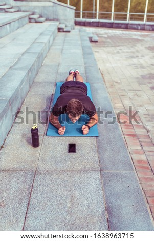 Male athlete, summer in city, fitness training, bottle shaker with protein and water, mobile phone, timer on smartphone. Workout abs, exercise abs exercise in plank #1638963715