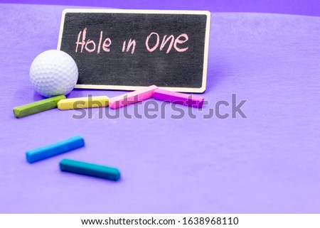 Golf, a hole in one or hole-in-one (also known as an ace, mostly in American English) occurs when a ball hit from a tee to start a hole finishes in the cup. Ball with word hole in on chalkboard