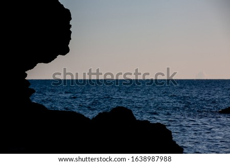 Silhouette of isolated cliff on sea coast with deep blue sea on sunset #1638987988