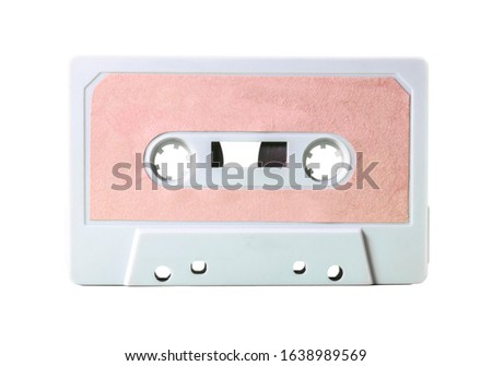 An old vintage cassette tape (obsolete music technology from the 1980s, having a great comeback). White plastic body, empty pink label. Isolated.  #1638989569