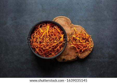 Dried cordyceps militaris mushroom in bowl on dark grey background.Cordyceps flower #1639035145