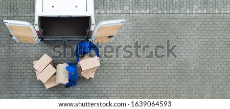 High Angle View Of Two Delivery Men Unloading Cardboard Box From Truck #1639064593