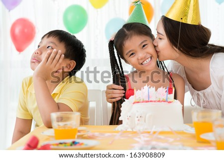 Image of a boy taking offence while his mother kissing his b-day sister on the foreground