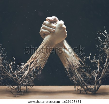 Two hands are holding together while twigs and braches are coming from the arms. Royalty-Free Stock Photo #1639128631