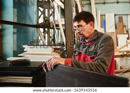 Process of production and manufacture of wooden furniture in furniture factory. Worker carpenter man in overalls processes wood on special equipment #1639143556