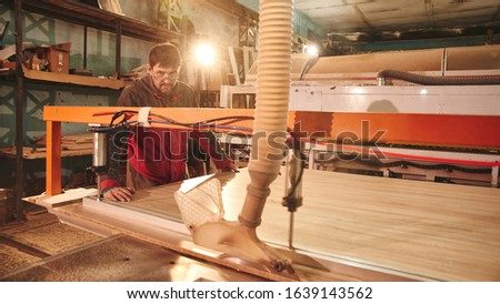 Process of production and manufacture of wooden furniture in furniture factory. Worker carpenter man in overalls processes wood on special equipment #1639143562