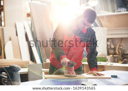 Process of production and manufacture of wooden furniture in furniture factory. Worker carpenter man in overalls processes wood on special equipment #1639143565