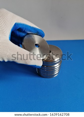 A gloved hand takes a washer from a stack of folded stainless steel washers on a blue surface and white background #1639162708