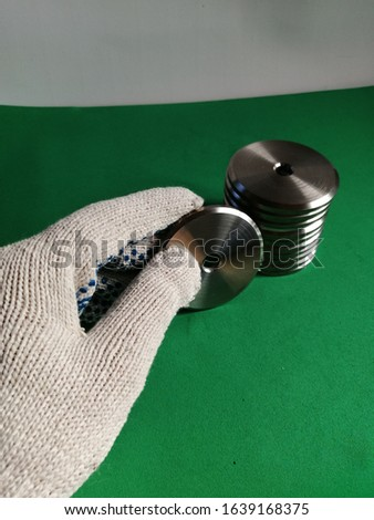 A hand in a glove holds a stainless steel washer from a stack of folded washers on a green surface and white background #1639168375