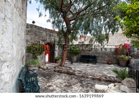 A secluded place, a place to relax, a bench and a tree in monastery Santa Catalina, Arequipa, Peru. #1639199869