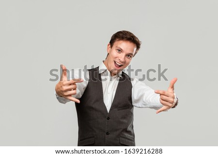 Confident businessman in a white shirt and grey vest holding hands in a gesture of rock music fan to express emotion of success. Concept of success #1639216288