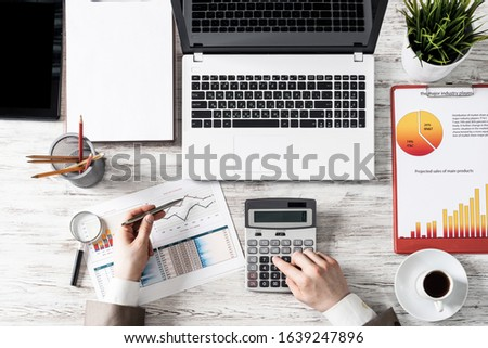 Businessman working at office desk with financial analytics. Top view office workplace with human hands calculating data. Flat lay table with laptop, calculator, business charts and cup of coffee. #1639247896