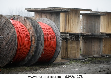 Wooden cable reels outdoors during a cold rainy day. #1639261378