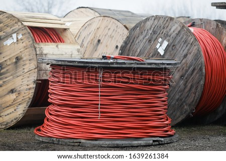 Wooden cable reels outdoors during a cold rainy day. #1639261384