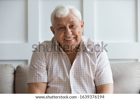 Close up headshot portrait of smiling mature man sit on couch at home look at camera posing for picture, happy positive senior male or optimistic grandfather feel good relax on comfortable sofa