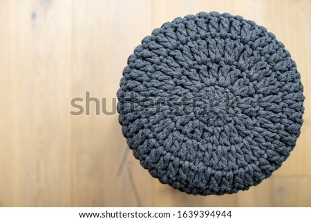 soft stool made of wool on a light-colored wooden parquet. Stool chair with gray knitted fabric cover. Interior furnishing supplies. Simple and handcrafted furniture #1639394944