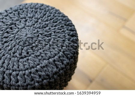 soft stool made of wool on a light-colored wooden parquet. Stool chair with gray knitted fabric cover. Interior furnishing supplies. Simple and handcrafted furniture #1639394959