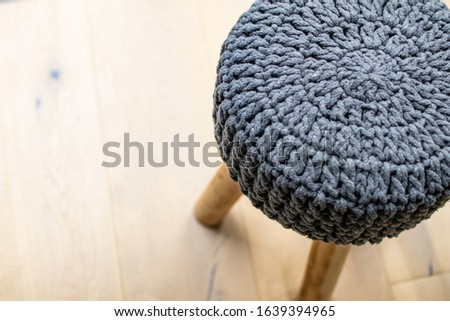 soft stool made of wool on a light-colored wooden parquet. Stool chair with gray knitted fabric cover. Interior furnishing supplies. Simple and handcrafted furniture #1639394965