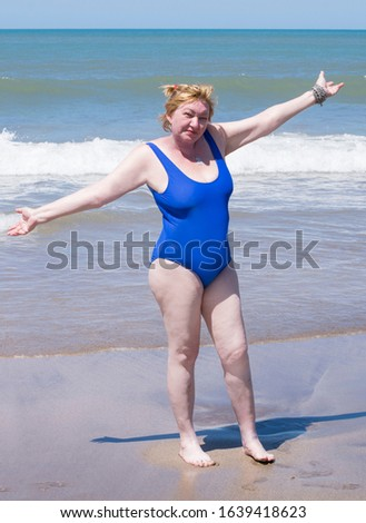 Adult, old age or  middle aged  good looking slim woman resting on the beach of the ocean ore sea and enjoying life #1639418623