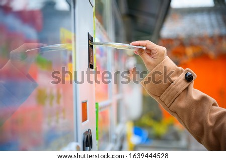 Hand of buyer insert push banknote money into slot water vending machine to buy a cold drink from machine services #1639444528