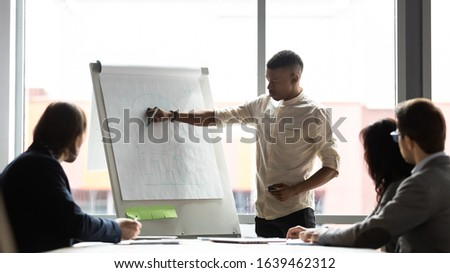 African American mentor giving flip chart presentation, drawing graphs on white board, business coach explaining strategy, presenting project statistics at workshop, training staff at briefing #1639462312