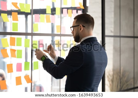 Side rear view focused businessman produces ideas search ways of solve problems attaching multi colored notes sheets on glass wall, prepare boardroom for negotiations corporate meeting concept #1639493653