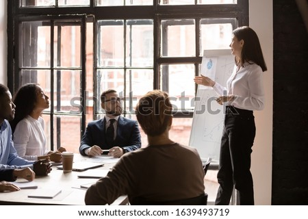 Diverse staff listen woman business trainer at corporate training in boardroom. Clients and firm representative take part in group meeting, presentation information new knowledge for audience concept Royalty-Free Stock Photo #1639493719