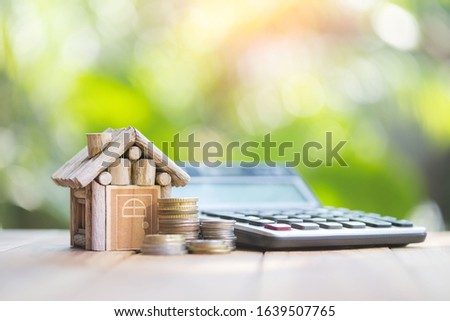 The house is placed beside the calculator, natural blurred green background. planning savings money of coins to buy a home concept for property, mortgage and real estate investment.to buy a house. #1639507765