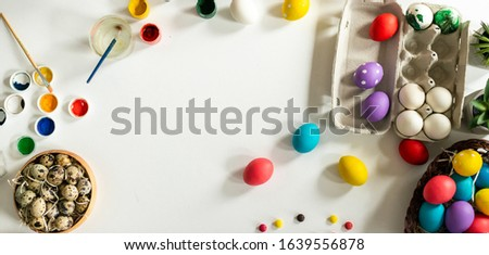 Easter background with copyspace. Colorful paints and eggs lie on the table.- Image #1639556878