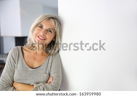 Senior woman standing against white wall #163959980