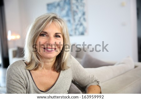 Smiling senior woman sitting in couch at home #163959992