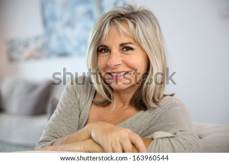 Smiling senior woman sitting in couch at home #163960544