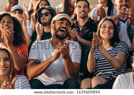 Group of people watching a sport event and cheering. Excited crowd of sports fans applauding sitting in stadium. #1639609894