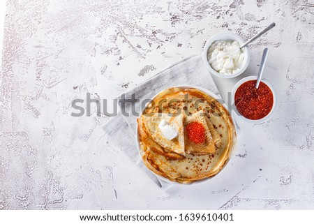 Traditional Russian Crepes Blini stacked in a plate with red caviar, fresh sour cream on light background. Maslenitsa Russian festival meal. Russian food, russian kitchen. Top view. Space for text #1639610401