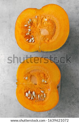 two halves of one pumpkin cut in half on a gray background, core, pulp and pumpkin seeds. #1639621072