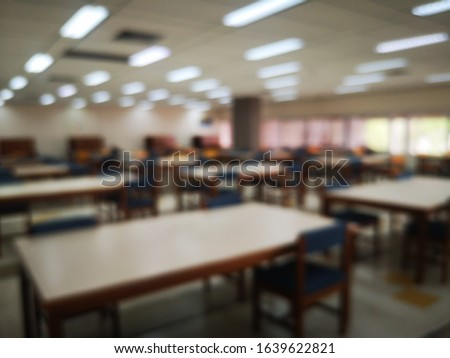 Blur or bokeh Interiors design wooden chairs and tables in the library room of university with the shelf books but nobody in the morning #1639622821