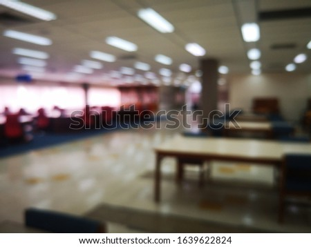 Blur or bokeh Interiors design wooden chairs and tables in the library room of university with the shelf books but nobody in the morning #1639622824