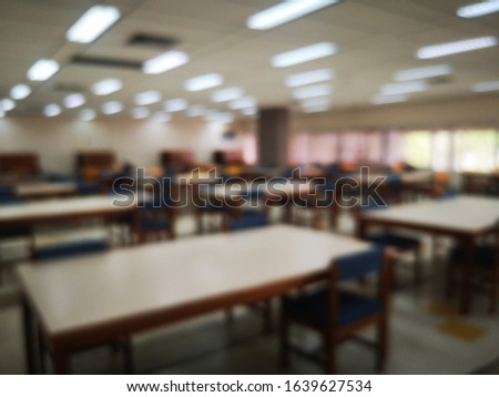 Blur or bokeh Interiors design wooden chairs and tables in the library room of university with the shelf books but nobody in the morning #1639627534