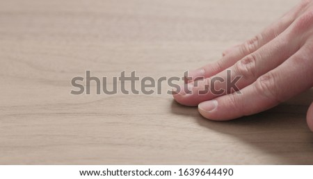 man hand touches black walnut board #1639644490