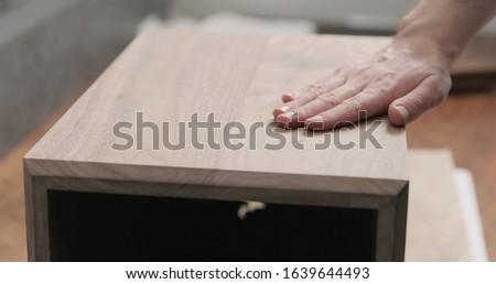 man hand touches black walnut storage box #1639644493